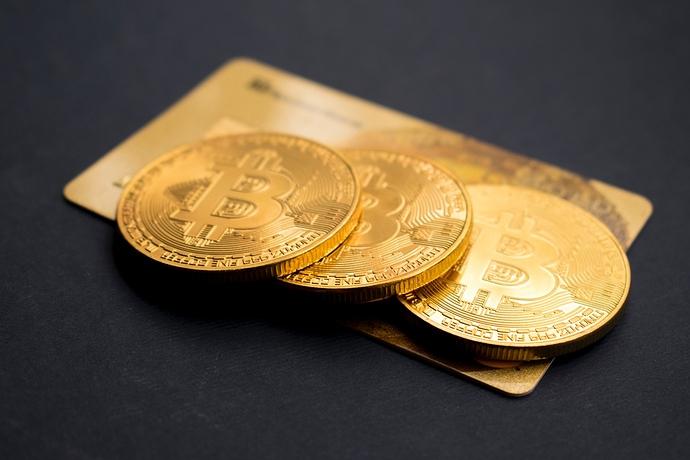 3 Bitcoin Münzen auf einer Kreditkarte