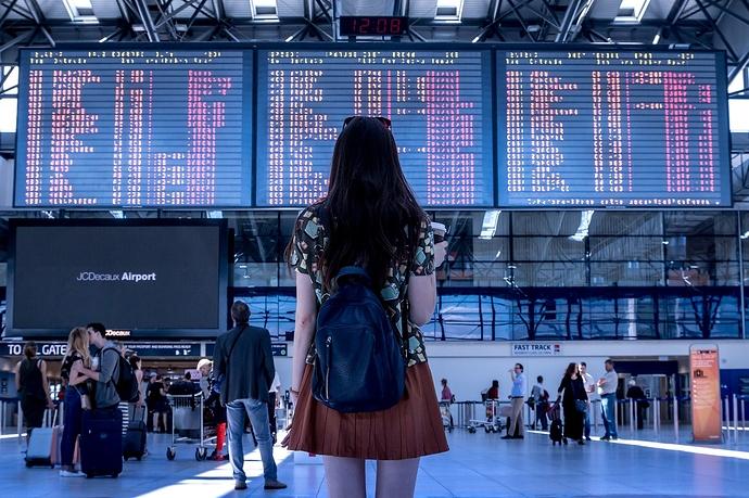 Frau vor Abfahrstafel am Flughafen