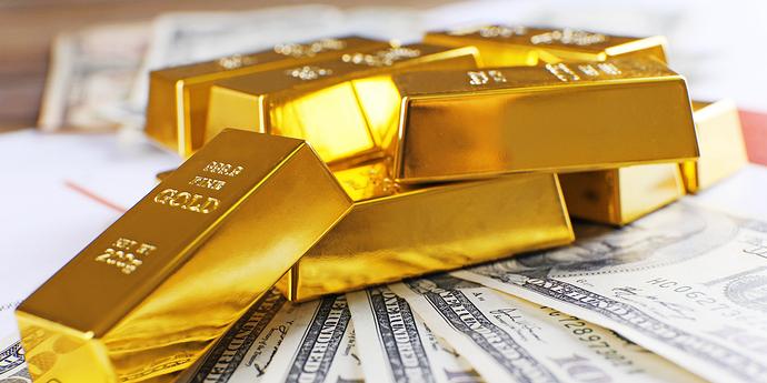 Goldbarren liegen auf Geldscheinen