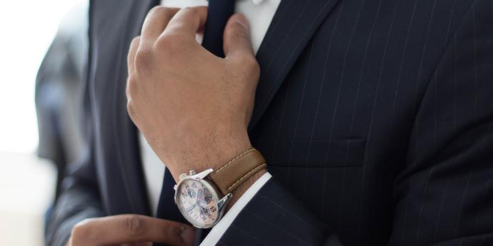 Mann im Anzug fasst sich an Krawatte