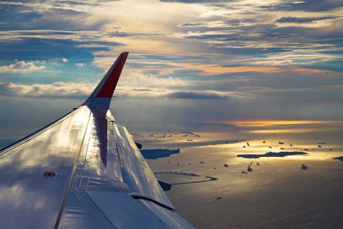 Flugzeugflügel vor Inselgruppe im Meer