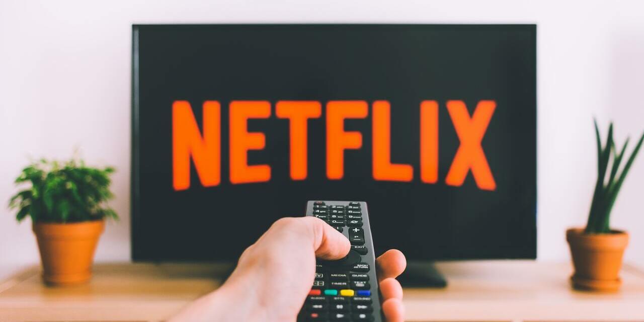 TV mit Netflix-Logo und Hand mit Fernbedienung