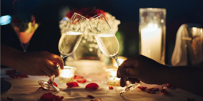 zwei Sektgläser stoßen in romantischer Stimmung an