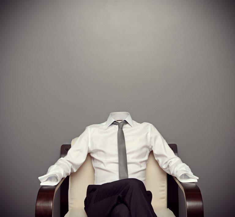 Person ohne Kopf sitzt auf Sessel