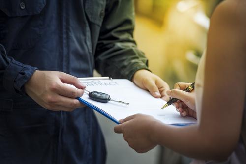 Frau unterschreibt Auto Kaufvertrag
