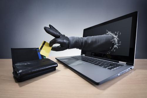 Hand kommt aus Bilschirm und stiehlt Kreditkarte